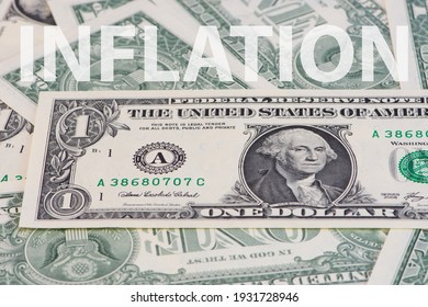 the word Inflation written in white capital letters over a photo of one Dollar banknotes