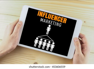 word influencer marketing on tablet in hand wood background