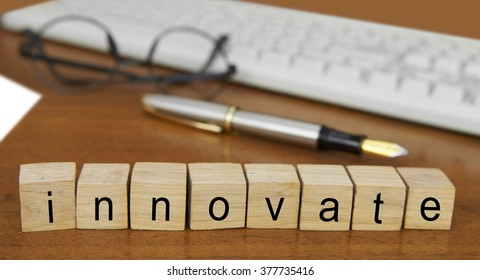 The word innovate on wood stamp stacking on desk with keyboard, vintage retro image style