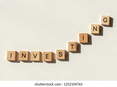 The word INVESTING spelled out in letter tiles as in a line graph chart going up in value.