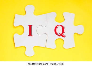 word IQ formed with puzzles in row on yellow background. concept image for test intelligence. Acronym IQ as Intelligence Quotient