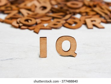 Word  IQ (Intelligence quotient ) made with wooden letters on a background of other blurred letters