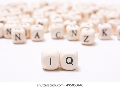 "The word ""IQ"" on the white  dice on a background of blurred letters. The concept of the mind, the intellect"