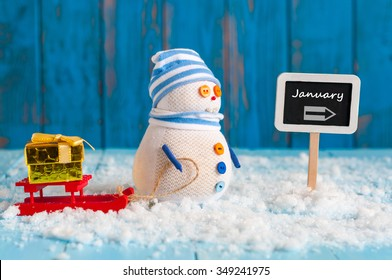 Word January written on direction sign and Snowman with red sled and new year gift. New Year decorations