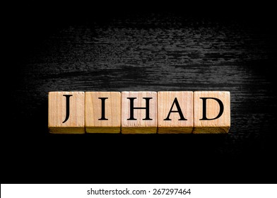 Word JIHAD. Wooden small cubes with letters isolated on black background with copy space available. Concept image.