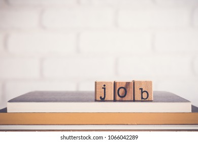 The word Job, alphabet on wooden cubes on top of books. Background copy space, minimal. Job application process, creating safe job procedures and work practices for employee and human resources.