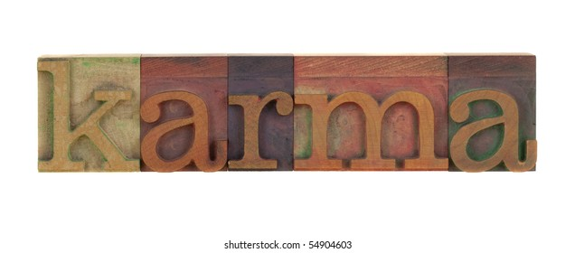 the word karma in vintage wood letterpress type blocks, stained by color ink, isolated on white