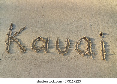 The word Kauai is written, drawn  in the sand of a beach in Kauai , Hawaii,  scratching the smooth wave washed sand