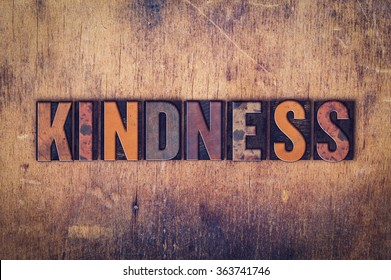 "The word ""Kindness"" written in dirty vintage letterpress type on a aged wooden background."