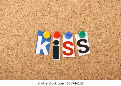The word Kiss In cut out magazine letters pinned to a cork notice board. KISS being the business word in planning strategy for Keep it Simple Stupid or Keep it Short and Simple