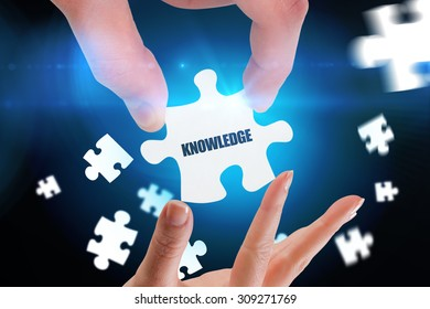 The word knowledge and hands holding jigsaw against blue background with vignette