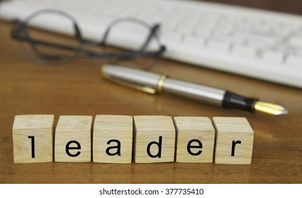 The word leader on wood stamp stacking on desk with keyboard, vintage retro image style