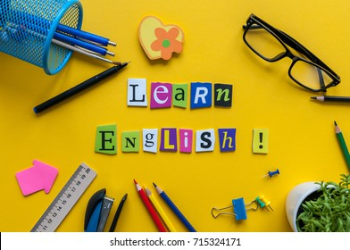 Word LEARN ENGLISH made with carved letters onyellow desk with office or school supplies, stationery. Concept of English language courses