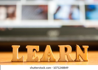 The word 'learn' made of wooden letters. wood inscription on a laptop background