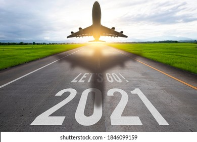 The word let's go written and 2021 and air plane on highway road in the middle of empty asphalt road , New year 2021 concept