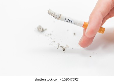 "The word ""Life"" on the cigarette in the hand burning on white background."