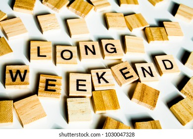 WORD LONG WEEKEND. Wooden letters spelling the word LONG WEEKEND on white background.