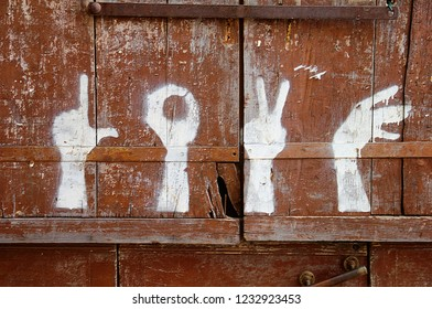 The word Love by means of gestures. White painted rising hand signs on the old wooden door in Besalu, Garrotxa, Province of Girona, Catalonia, Spain, Europe