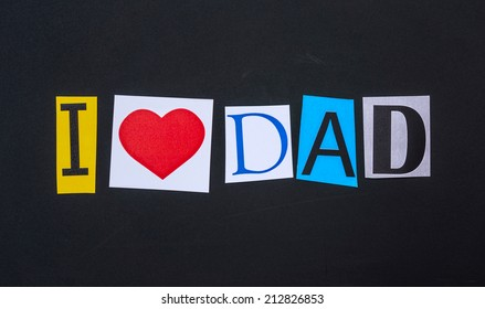 The word i love dad in cut out magazine letters on blackboard