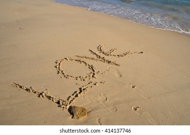 The word Love drawn on the beach sand. Honeymoon vacations and Valentine's Day theme