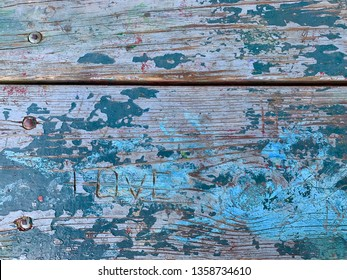The word love etched into distressed wood with deep blue and teal paint.
