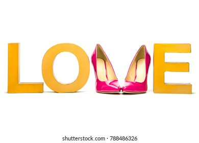 Word LOVE in golden vintage letters and pink high heels shoes.