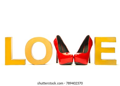 Word LOVE in golden vintage letters and shiny red high heels shoes.