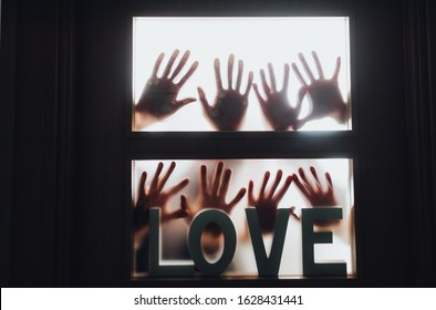 Word - LOVE. Hands and fingers of people in silhouette against the background of a door with a window, locked and asking for help. Horror. Swingers, group sex, swedish family, relax and orgy concept.
