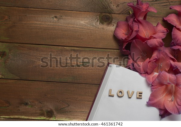 The word love a lot of hearts, flowers on a background of book on a wooden table. Back to school copy space. Education background.