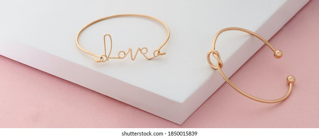 Word love and knot shape golden bracelets on pink and white background