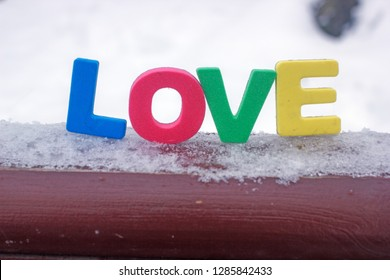 The word love in multicolored letters on white snow, a background about love, a background to the day of lovers, multi-colored letters, the word loveon white snow, a background about love, a backgr