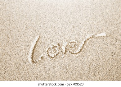 The word LOVE on wet brown sand on beach with noon light effect background.