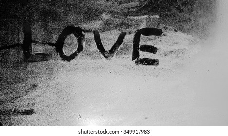 """The word """"Love"""" on the window in the rain,black and white,horizontal photo"""