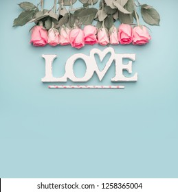 Word love with roses border on pastel blue background, top view with copy space . Valentines day or abstract love concept