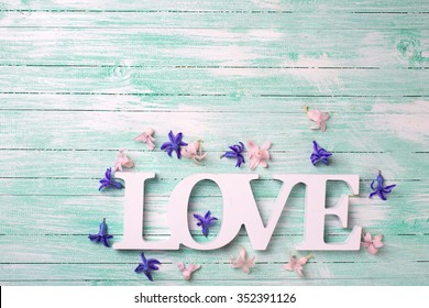 Word love and small pink and violet flowers on turquoise wooden background. Selective focus. Place for text.