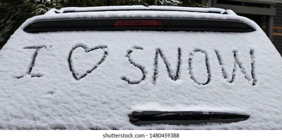Word of  I love snow writing on the car window.
