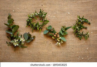 The word 'love' spelt from Australian native flowers on natural hessian background.