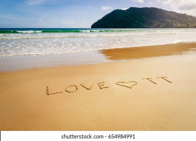 Word Love TT Trinidad and Tobago written on the beach sand in Maracas Bay Beach