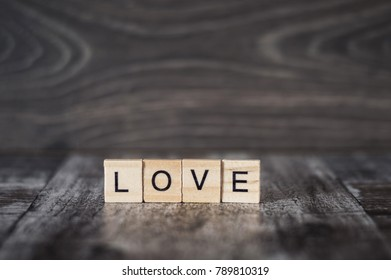 the word love from wooden cubes on a dark wooden background