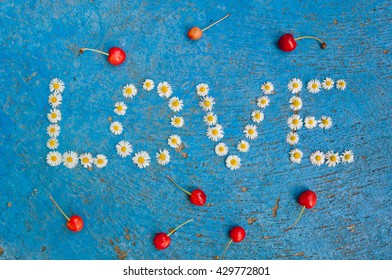 The word Love written of daisy flowers on textured blue background, top view