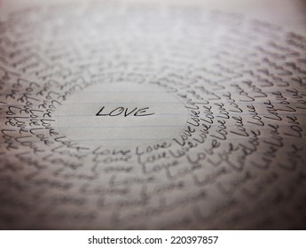 the word love written on a lined piece of school paper in ink with a vignette and a circle of love (very shallow depth of field - focus on the bottom of the word love)
