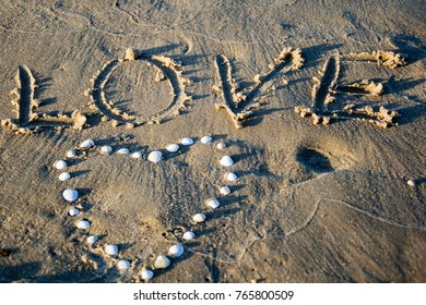 Word love written on sand at beach and heart of shells, symbol of love, summer time