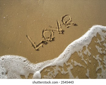 The word love written in the sand on a beach as ocean water approaches