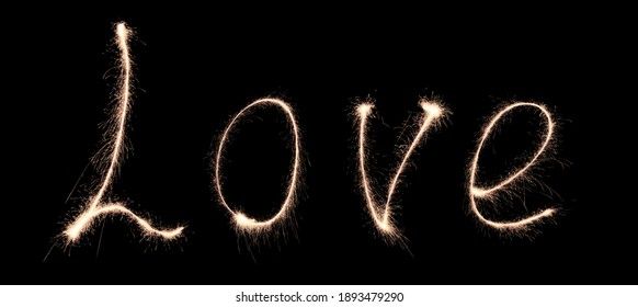 the word love is written with sparklers in the dark, background for valentine's day, february 14 holiday