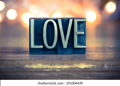 The word LOVE written in vintage metal letterpress type on a soft backlit background.