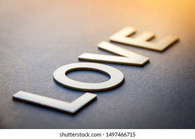 Word love written with white solid letters on a board
