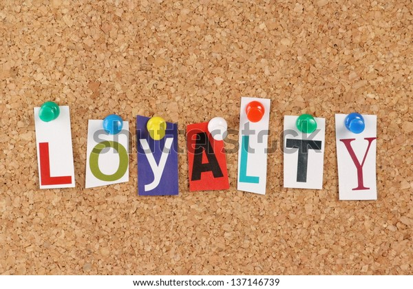 The word Loyalty in cut out magazine letters pinned to a cork notice board. Used in  business the phrase might refer to customer or brand loyalty.