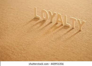 """The word """" loyalty """" wooden letters wooden on cork board background."""