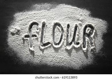 Word made of flour on dark table