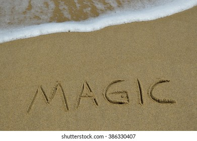 The word magic written in the sand at the beach